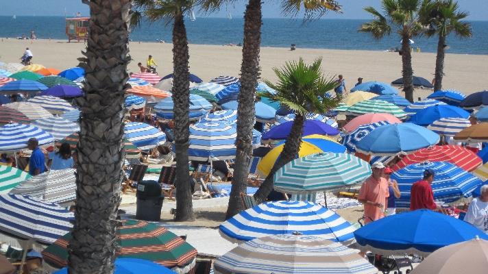 Beach Volleyball Players Strategize Under Umbrellas